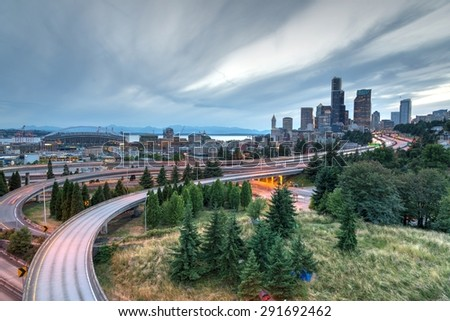 SEATTLE, WASHINGTON, US - JUNE 23, 2015 - Seattle skylines and highway traffic motion in the sunset with cloud storm. The view from Rizal Park in Seattle, Washington, US. Motion and high speed concept - stock photo