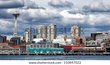 Seattle waterfront and skyline under dramatic dark clouds - stock photo