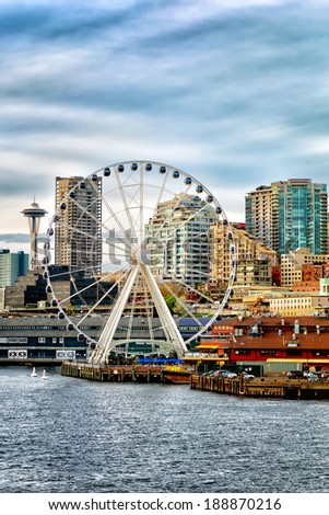 Seattle waterfront and skyline, with the Great Wheel ferris wheel in the foreground and the iconic Space Needle in the background. Copy space for text. - stock photo