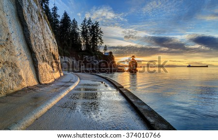seawall and rock wall at sunset, with famous Siwash Rock in the sea water, Stanley Park, Vancouver, British Columbia, Canada - stock photo