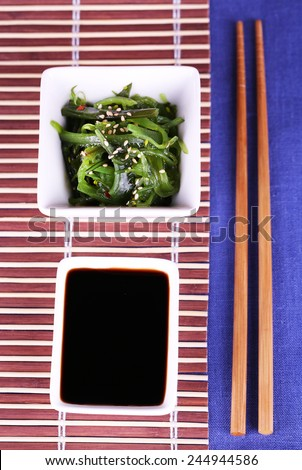 Seaweed salad in bowl with sticks on bamboo mat and color table background - stock photo