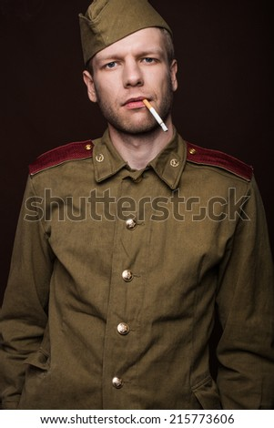 Second world war russian soldier smoking cigarette. Studio portrait isolated on brown background - stock photo