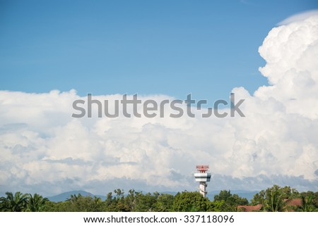 Secondary radar tower nearby the airport with big towering cumulonimbus cloud and blue sky - stock photo
