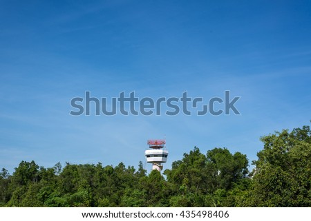 Secondary surveillance radar tower for tracking postion of the aircraft behind the trees with blue sky - stock photo