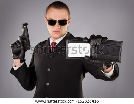 Secret agent in a black suit with a red tie, gun and badge - stock photo