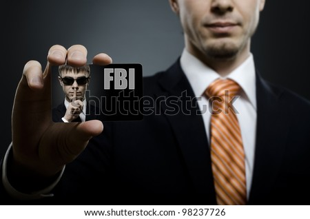 secret agent in black costume and orange necktie reach out on camera and show  visiting card, close up - stock photo