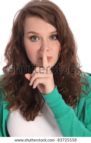 Secret hand sign by cute teenager school girl with long brown hair and big blue eyes. She has a finger over her lips indicating quiet or not speaking.