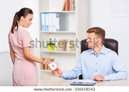 Secret note. Young appealing woman stops at the desk to pass a love note to her romantic partner.  - stock photo