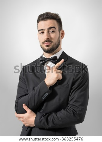 Secret service agent or bodyguard mimic pistol with hand gun gesture sign. Desaturated portrait over gray studio background with retro vignette.  - stock photo