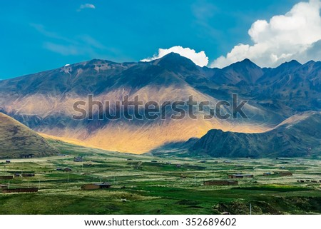 Secret valley of the Incas with farms at sunset on the background of blue sky - Peru, Latin America - stock photo