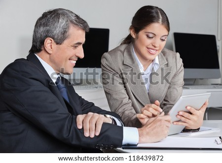 Secretary and businessman doing time management with tablet pc in the office