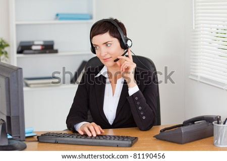 Secretary calling with a headset in her office - stock photo