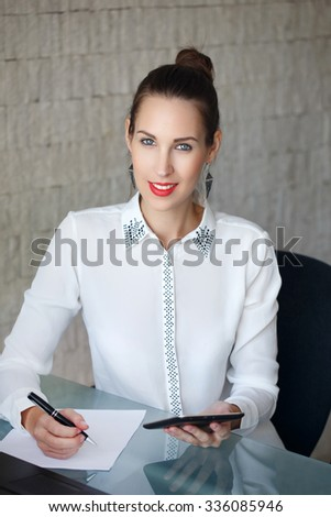 Secretary holding tablet and write on blank paper in office - stock photo