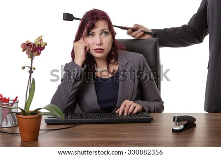 secretary sitting at desk with a mans hand holding a riding whip on the back of her chair - stock photo
