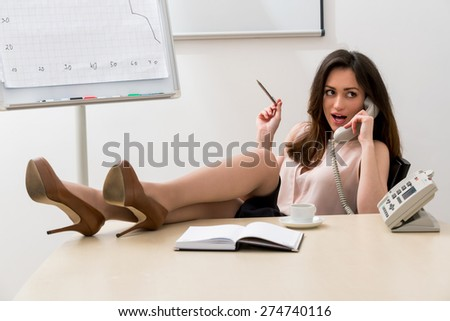Secretary speaks on the phone. Business woman with her legs on the table. Clerk at the workplace.