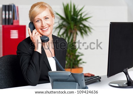 Secretary talking on phone with client, looking at you - stock photo