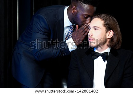 Secretary whispering something into the ears of his boss - stock photo