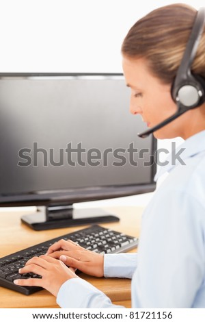 Secretary with a headset working with computer in her office - stock photo