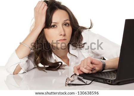 secretary with a laptop looking at his watch in boredom on white background - stock photo
