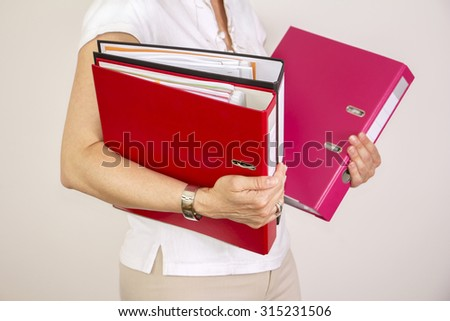 Secretary woman holding stack of office binders - stock photo