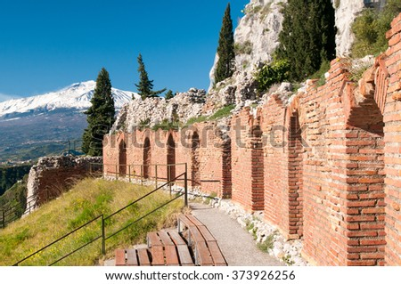 Section of the upper perimetral arcade of the greek theater of Taormina, Sicily, with snowy mount Etna in the background - stock photo