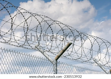 Security barrier with a barbed wire fence - stock photo