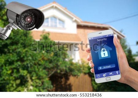 Security camera and smart home app, private house on the background
