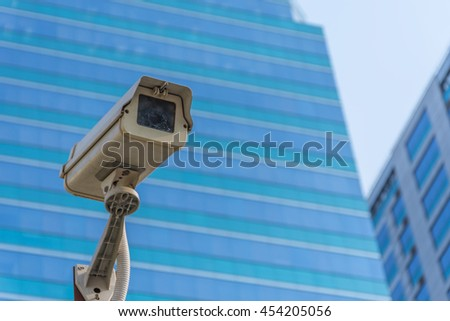 Security camera (CCTV) for safety on blue sky and city background