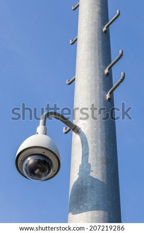 Security camera, CCTV on blue sky background for close monitoring - stock photo