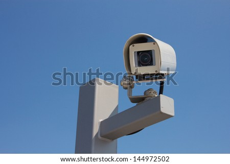 Security camera facing left before the background of a clear blue sky. - stock photo