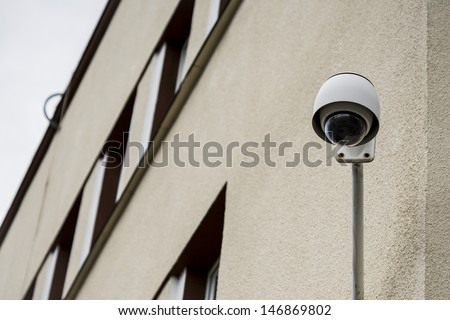 Security camera on a building set to the observations of the street and people.