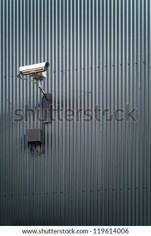 Security camera on a wall of corrugated iron - stock photo