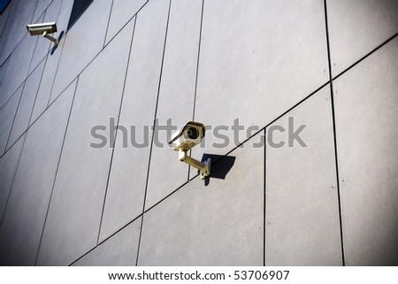 Security camera on dark grunge building - stock photo