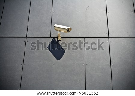 Security camera on gray modern building wall, technology in city
