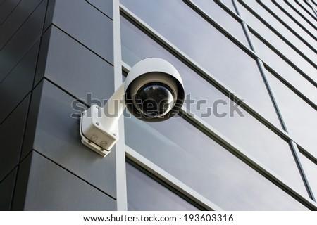 Security camera on modern building facade - stock photo