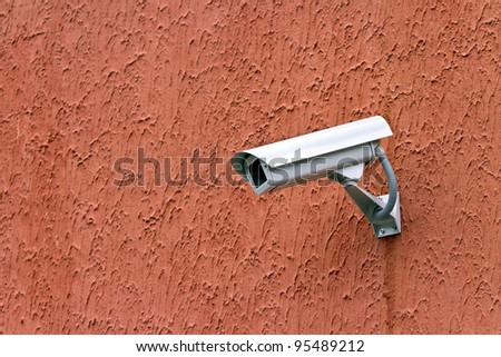 Security camera on red textured wall
