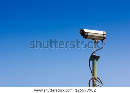 Security camera with a sky background - stock photo