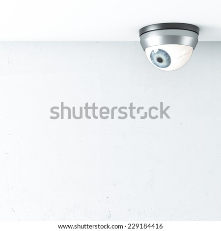security camera with blue eye on ceiling - stock photo
