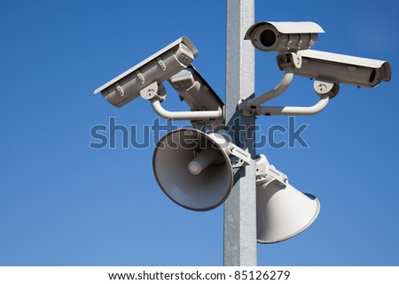 Security cameras and speakers on pole over blue sky