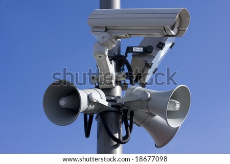 Security cctv camera and speakers  in front of blue sky - stock photo