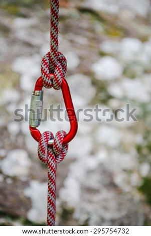 Security climb, carabiner with rope on rock background - stock photo