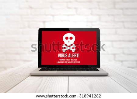 security concept: digitally generated laptop on a wooden table with virus alert. Screen graphics are made up. - stock photo