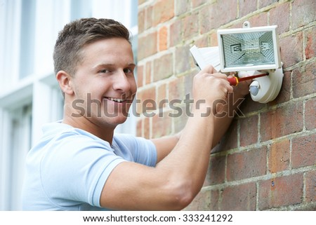 Security Consultant Fitting Security Light To House Wall - stock photo