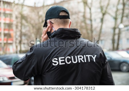 Security Guard In Black Uniform Listening With Earpiece - stock photo