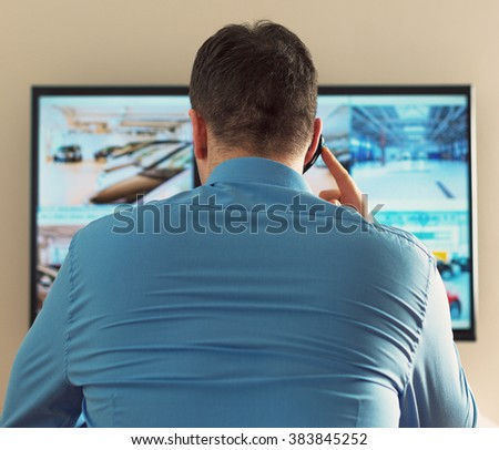 Security guard monitoring video in security room. From the back. - stock photo
