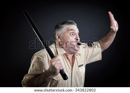Security guard whistling and holding firmly baton in one hand raised in the air ready for action. - stock photo