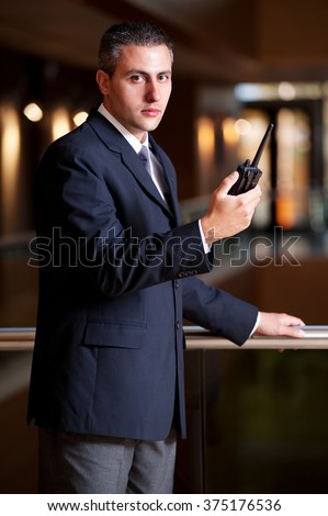 security guard with a portable wireless transceiver on a blurry background