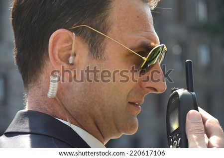 Security guard with glasses and walkie-talkie in his hand - stock photo