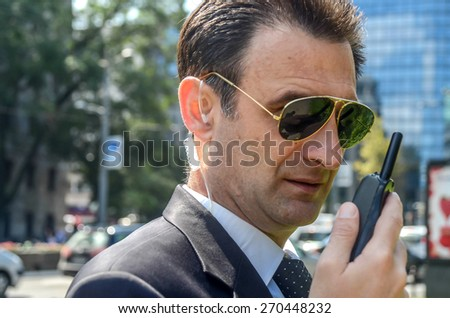 Security guard with glasses and walkie-talkie in his hand, SOFT FOCUS - stock photo