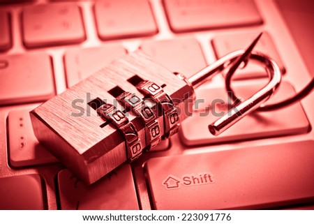 security lock on computer keyboard with a fish hook / computer data theft concept / phishing - stock photo